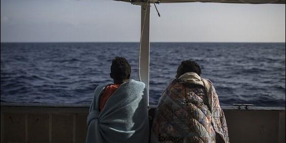 dos-migrantes-hablan-y-observan-el-mar-desde-el-open-arms_560x280